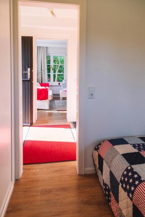 Ferienhaus Möwe Jonathan - Appartement Schlafzimmer, Eingangsbereich mit Blick auf den Wohnbereich